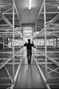 a guy passing empty industrial shelves