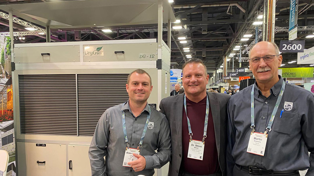 Signify's Martin Boerema and Blake Lange posing in front of a DG-12 with DryGair's Steve Millett